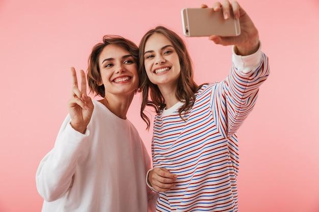 Друзья женщины, изолированные над розовой стеной, берут sefie по мобильному телефону.