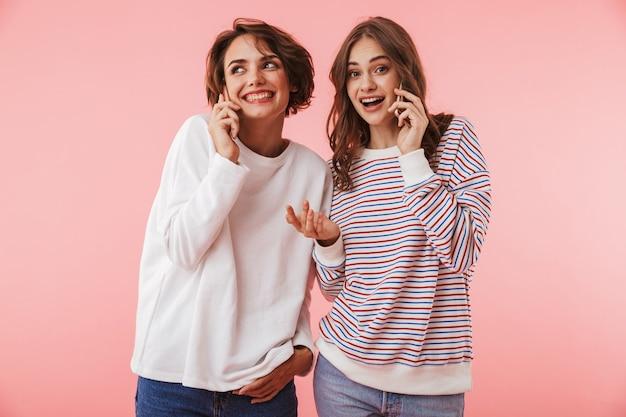 Друзья женщины, изолированные на розовой стене, разговаривают по мобильным телефонам.