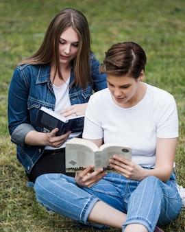 Женщины-друзья читают в парке Бесплатные Фотографии
