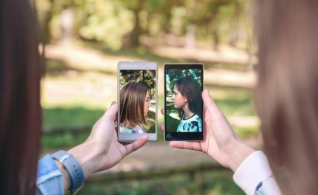 Подруги-женщины показывают смартфоны со своими портретными фотографиями, сделанными на фоне леса
