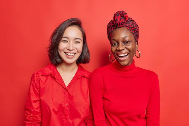 여자 친구 미소 긍정적으로 좋은 하루를 보내고 자유 시간을 함께 보내고 밝은 빨간색 옷을 입고 생생한 스튜디오에서 서로 옆에 서 있습니다