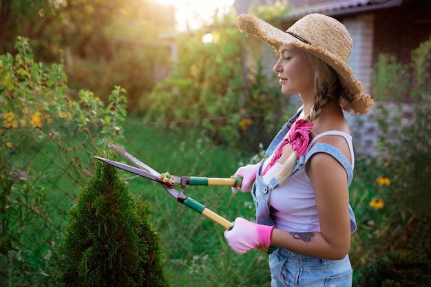 女性の庭師。オーバーオールと麦わら帽子のセクシーな女の子が芝生をかみます。ランドスケープデザインと植物の世話。