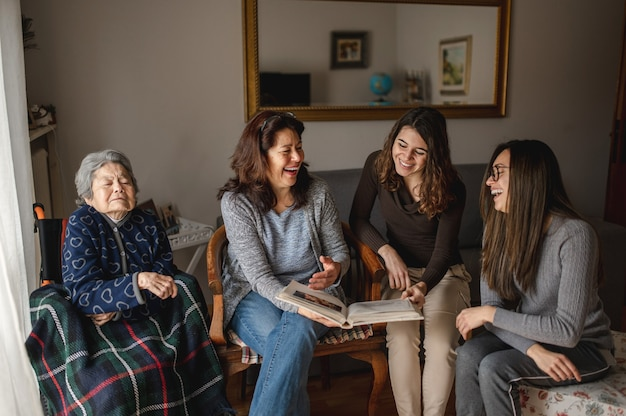 Women generation with old sick grandmother sitting in wheelchair next to daughter and granddaughters looking a photo album