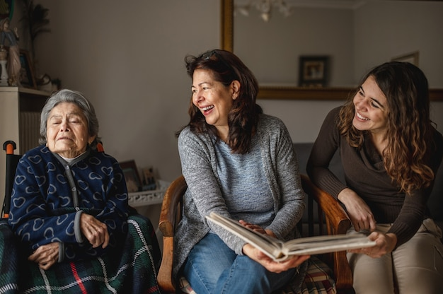 Women generation with old sick grandmother sitting in wheelchair and smiling daughter and granddaughter looking a photo album.