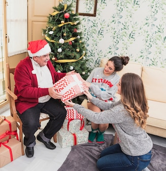Women giving gift box to old man