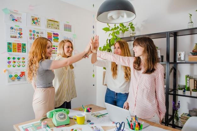 Женщины, дающие высокие пять в должности