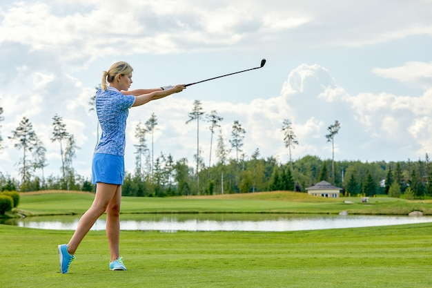 Women golfing time holding golf equipment on green field