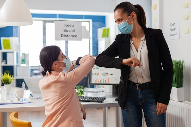 Le donne salutano nel nuovo ufficio normale toccando i gomiti che urtano mantenendo le distanze sociali come prevenzione della sicurezza indossando la maschera facciale durante la pandemia globale con covid19.
