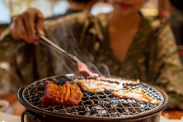 숯불 난로, 한국식 바베큐 또는 야키니쿠 스타일로 생 돼지 고기 구이.