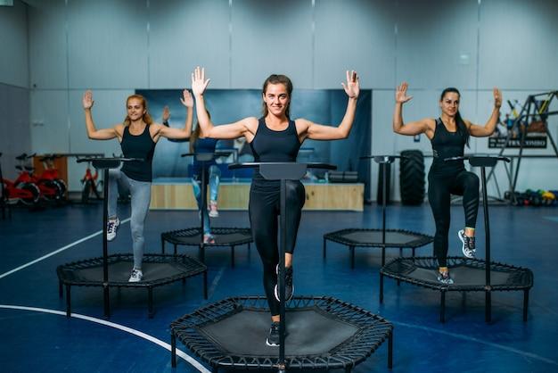 스포츠 트램폴린, 피트니스 운동에 맞는 운동을하는 여성 그룹. 체육관에서 여성 팀워크입니다. 에어로빅 클래스