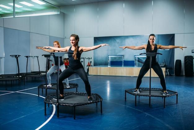 Группа женщин делает упражнения на спортивном батуте