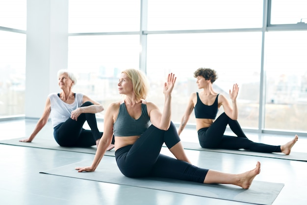 Women group doing yoga next to a large window