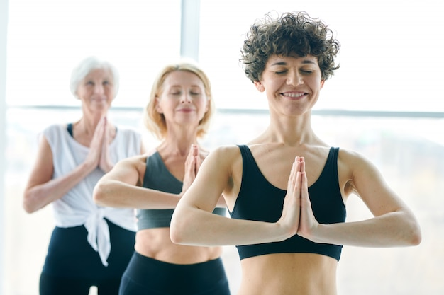Women group doing yoga and meditating next to a large window