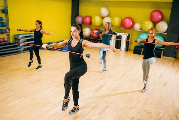 フィットネストレーニングで運動する女性グループ。ジムでの女性のスポーツチームワーク。