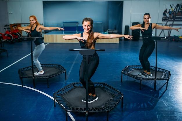 スポーツトランポリン、フィットネストレーニングの女性グループ。ジムでの女性のチームワーク。有酸素クラス