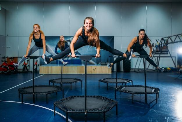 Women group on sport trampoline, fitness workout. female teamwork in gym. aerobic class