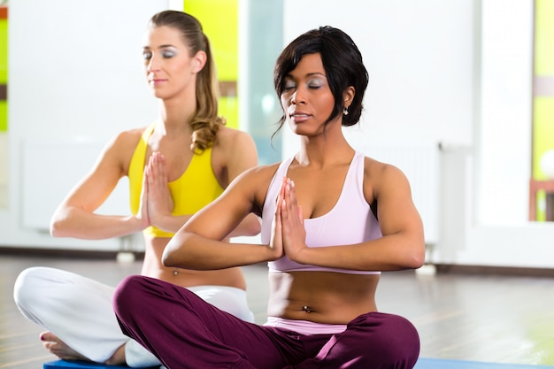 Women in the gym doing yoga exercise for fitness