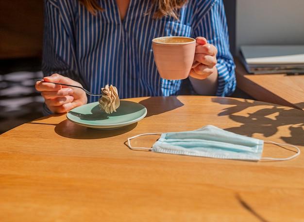 Женская рука и чашка кофе, сладкий десерт и медицинская маска для лица на деревянном столе в кофейне крупным планом