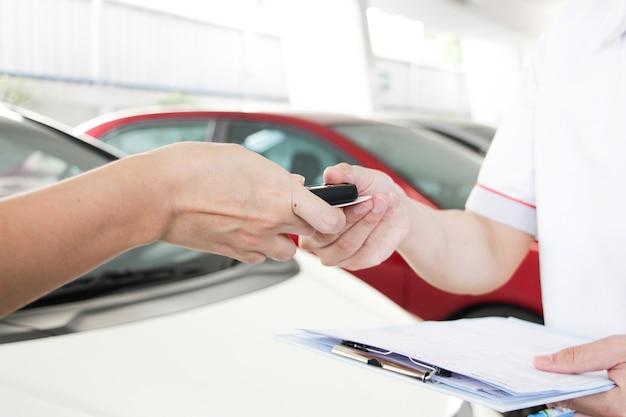 여자 손과 남자 손은 자동차 배경의 현대적인 자동차 키를 제공합니다. 교통 개념입니다. 새 자동차 개념을 판매하거나 구매합니다. 유지 보수 개념입니다.