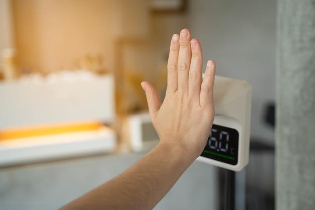 デジタル自動体温測定機でカフェに入る前に女性が手で体温をチェック