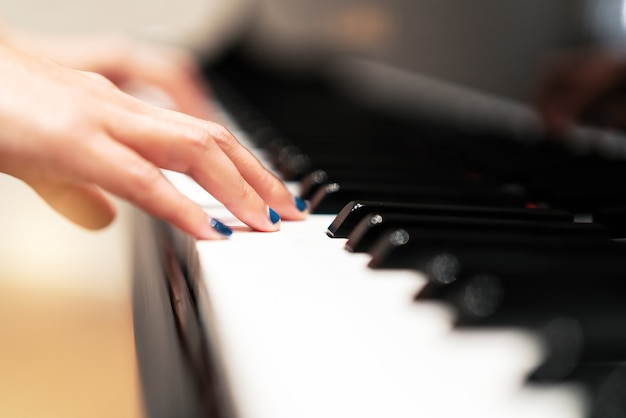 Women hand on classic piano keyboard closeup, music instruments concept