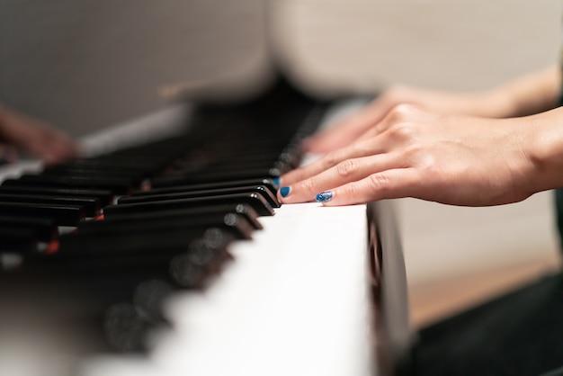 Women hand on classic piano keyboard closeup