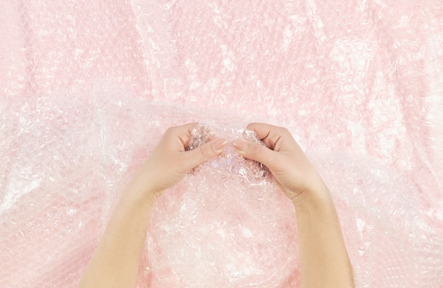 Women hand clench and slam antistress bubble wrap
