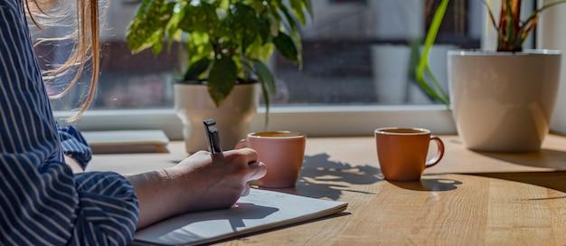 Женщины рука крупным планом писать ручкой в блокноте или планировщик, делая заметки в кафе с чашкой кофе и ...