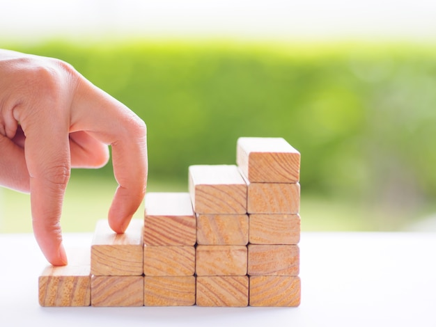 Women hand finger walk on stacked wooden block like stairs. business growth concept.