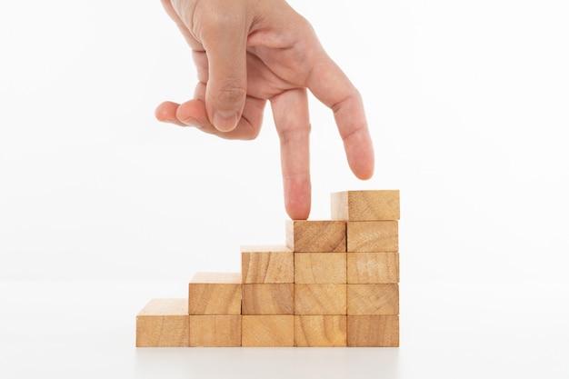 Women hand finger walk on stacked wooden block.
