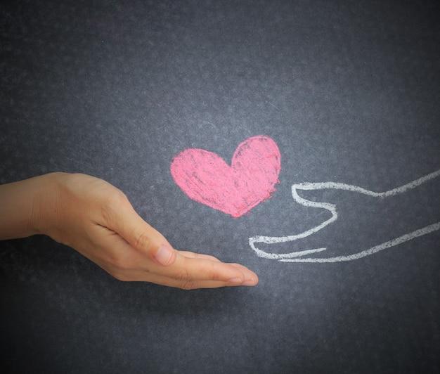 女性の手は、白板の背景に落書きの心に落書き心を与えます。
