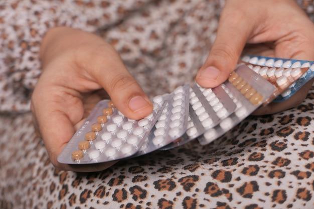 女性の手が金色の避妊薬をクローズアップ