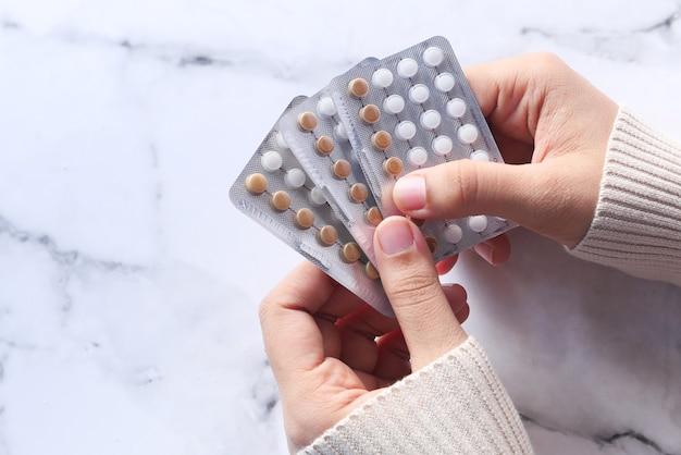女性の手が金色の避妊薬をクローズアップ。