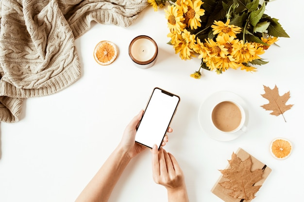 Women hand hold cell phone. home office table desk workspace. flat lay, top view girl boss business concept. blanket, flowers bouquet, leaves, coffee cup