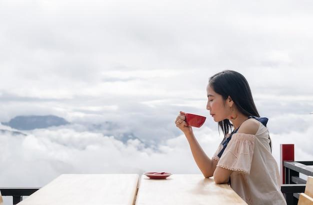 여자 손 잡고 아침 해의 커피 컵