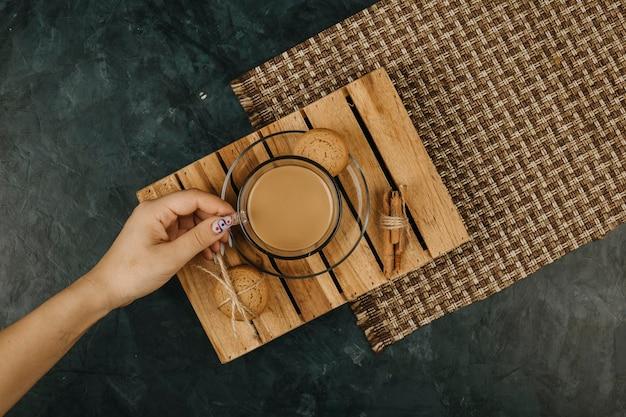 紺色の背景の木製テーブルにコーヒーを持っている女性の手