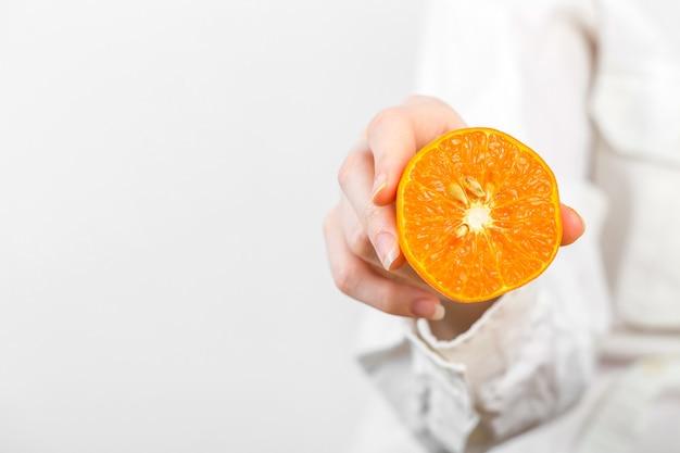 白で隔離されるオレンジを持っている女性の手