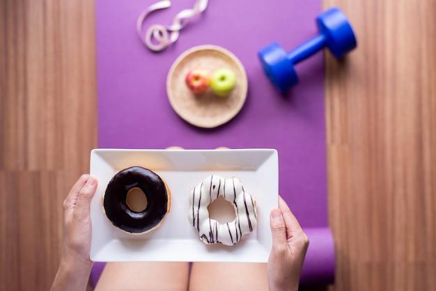 요가 매트에 서서 구운 도넛을 들고 있는 여성, 건강한 식단, 다이어트 개념, 탑 뷰