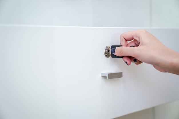 Women hand holding the black simple key to open the white wardrobe. clear background.