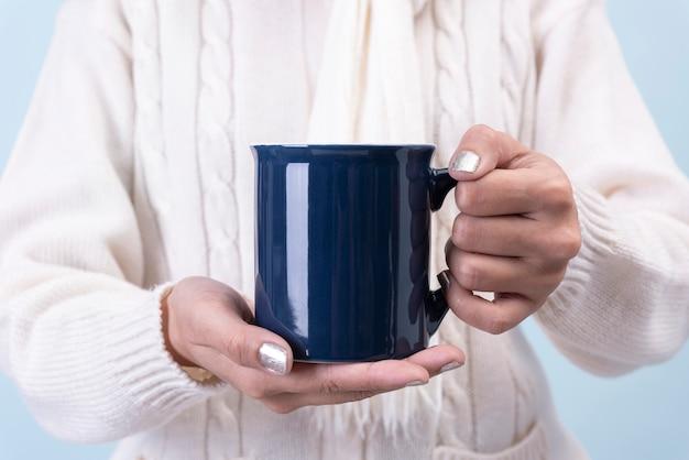 Женщины рука синий керамический кофе кубок. макет для креативного рекламного текстового сообщения или рекламного контента.