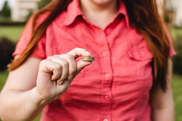 여자 손을 잡고 동전, 비즈니스의 개념, 여름 날에 자연 녹색 표면