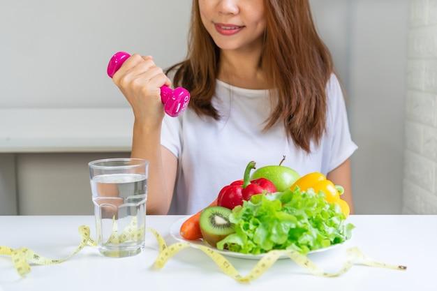 흰색 테이블 배경에 과일 야채 물과 테이프 측정 아령을 들고 여자 손