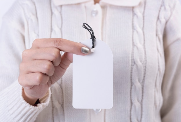 Women hand holding gift tag made from recycled card on white background. promotion sale for christmas and happy new year.