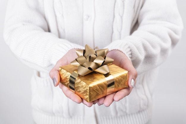 Women hand holding gold gift box on white background.