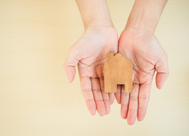 Women hand holding house decoration made of wood, promoting work from home and social distancing to reduce spreading of coronavirus infection.