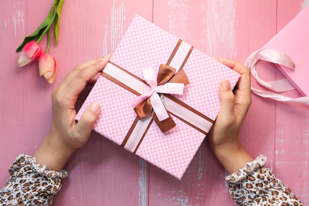 ピンク色のギフトボックス、上面図を持っている女性の手。
