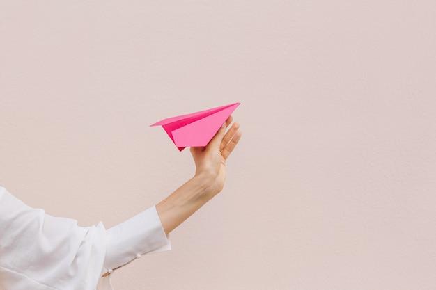 Женщины рука розовый бумажный самолетик на бежевом фоне. копировать пространство