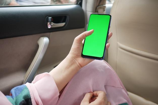 차에 녹색 화면이 있는 스마트 폰을 들고 있는 여성