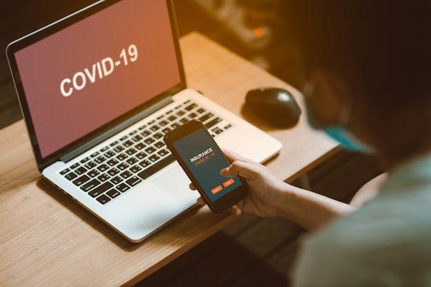 Женщины рука смартфон, чтобы зарегистрироваться или войти в систему для страхования от коронирусного вируса (covid-19) онлайн. после проверки новостей распространяется вирус в интернете. страховая концепция