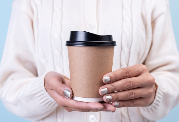 Women hand holding take away paper coffee cup. mockup for creative advertising text message or promotional content.